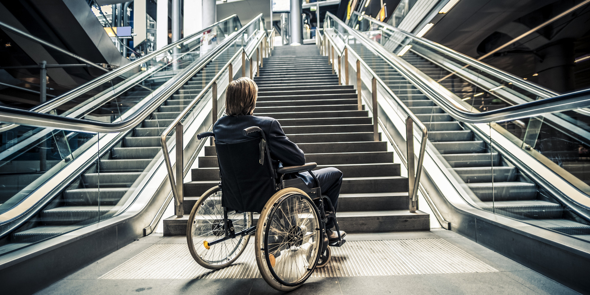 Businessman on a wheelchair against modern stairs